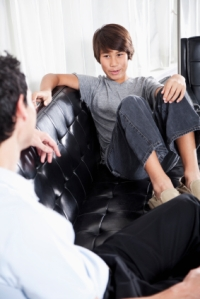 Father and son talking in living room