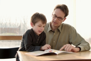 dad and son looking at workbook