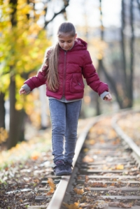 Girl walking down train tracks