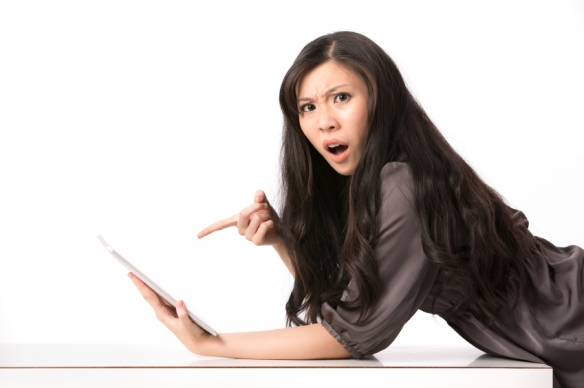 Shocked woman pointing at her digital-tablet.