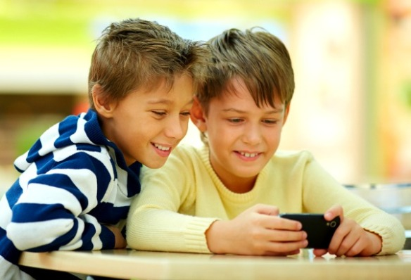 Two boys watching smartphone photos