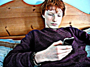boy in bed with mobile